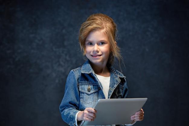 Bambina che si siede con il tablet