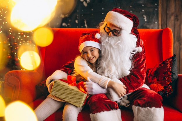 Bambina che si siede con santa e regali a natale