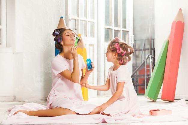 Bambina che si siede con sua madre e gioco