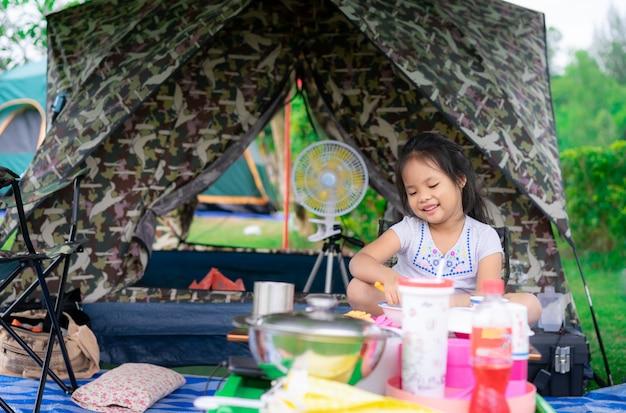 Bambina che si siede davanti alla tenda mentre andando in campeggio. il concetto di attività all'aperto e avventure in natura.