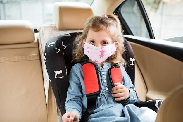 Bambina che si siede in un'automobile in una mascherina medica. covid-19 concetto di diffusione globale pandemica del coronavirus.