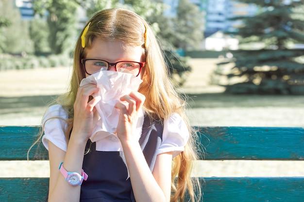 Bambina che si siede nel parco che starnutisce con il fazzoletto