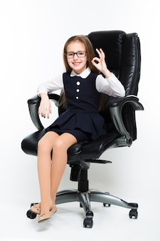 Bambina che si siede nella sedia che mostra segno giusto vestito come una donna di affari