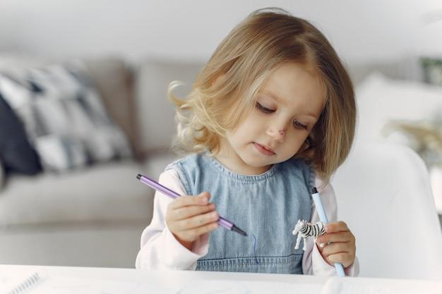 Bambina che si siede su una tabella con i libri