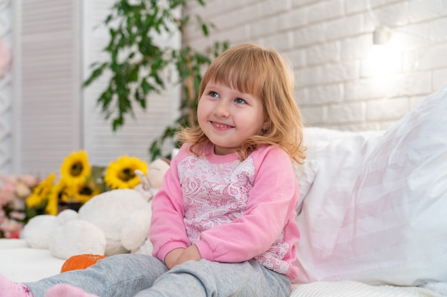 Bambina che si siede sul letto a casa