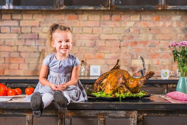 Bambina che si siede sul tavolo con tacchino arrosto