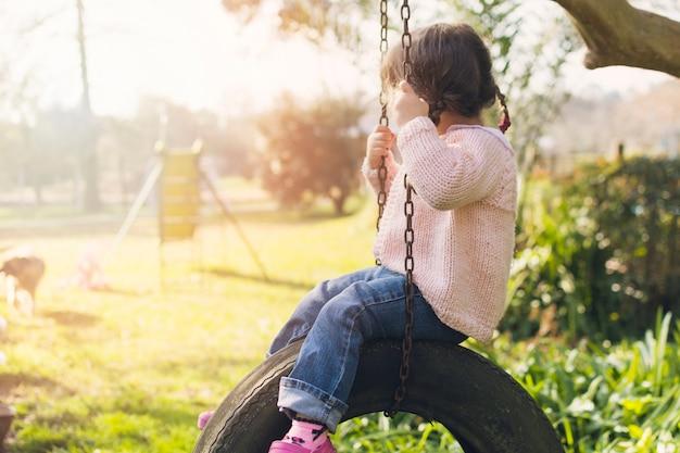 Bambina che si siede sull'oscillazione della gomma dell'automobile nel parco