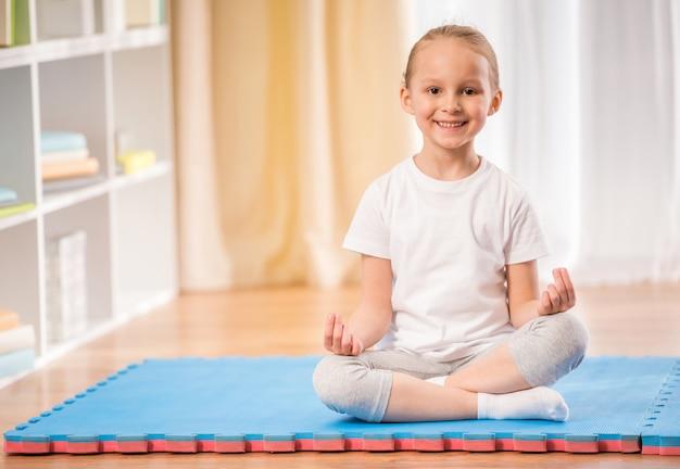 Bambina che si siede sulla stuoia di esercitazione.