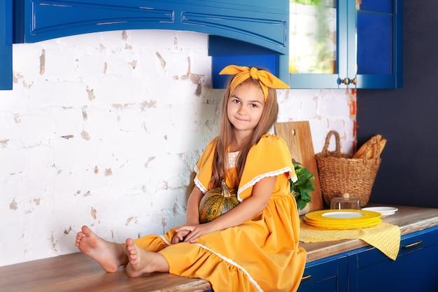 Bambina che si siede sulla superficie di lavoro della cucina in attesa di colazione. ragazza allegra e birichina in cucina. alimentazione sana, vegetarismo, verdure. arredamento cucina autunnale. halloween. rustico