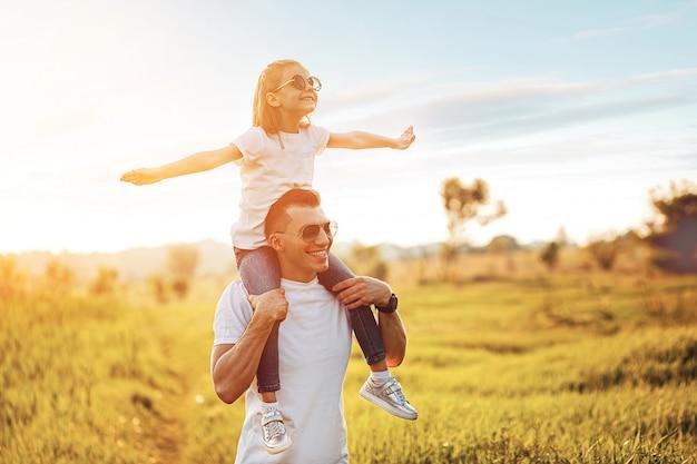 Bambina che si siede sulle spalle e sulla risata del padre