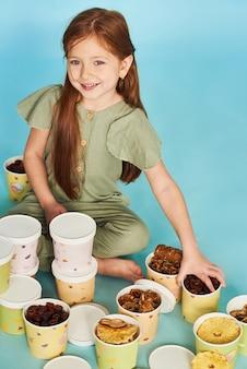Bambina che si siede vicino a molti pastelli e patatine fritte in tazze di carta variopinte su fondo blu.