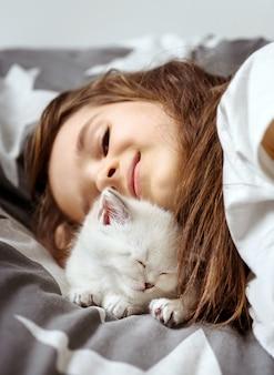 Bambina che si trova sul sofà con il gatto bianco