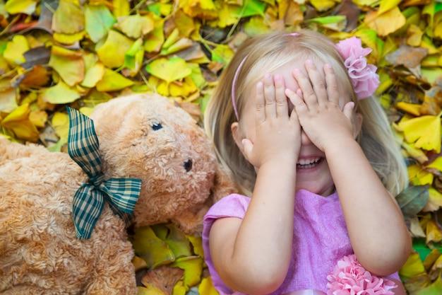 Bambina che si trova sulla strada sulle foglie cadute con la sua amica un orsacchiotto