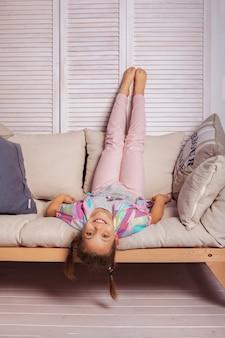 Bambina che si trova sullo strato sottosopra. infanzia