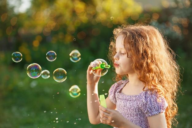 Bambina che soffia bolle di sapone nel parco estivo.
