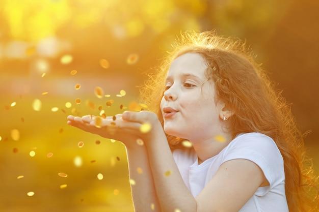 Bambina che soffia coriandoli d'oro con la sua mano.