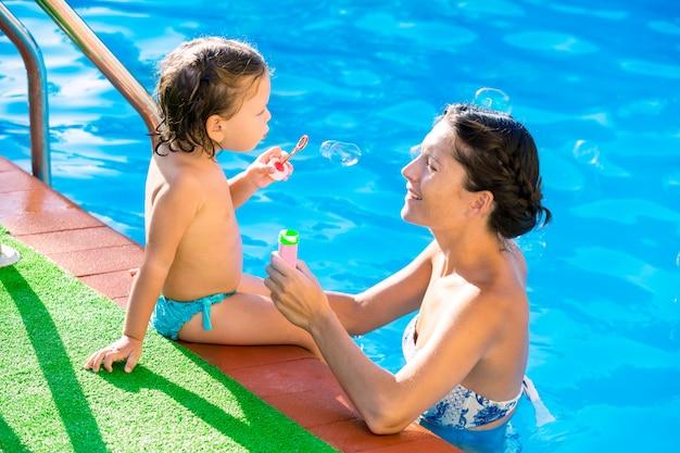 Bambina che soffia gli impulsi del sapone con la madre in piscina