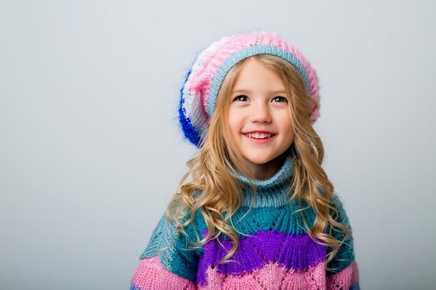 Bambina che sorride in cappello e maglione tricottati sull'isolato bianco