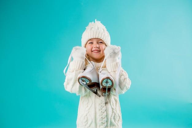 Bambina che sorride in un cappello e maglione bianchi di inverno