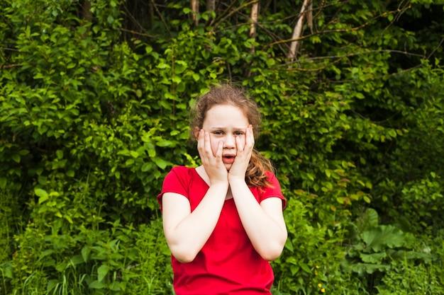 Bambina che sta nel parco che esamina macchina fotografica con l'espressione impaurita