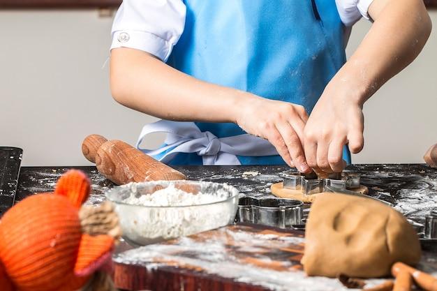 Bambina che taglia i biscotti della pasta del pan di zenzero