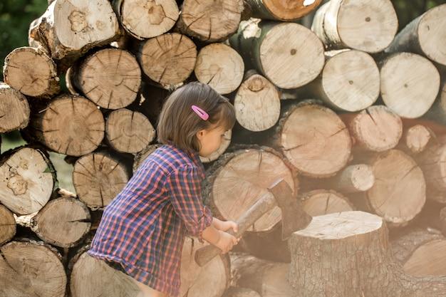 Bambina che taglia legno a pezzi
