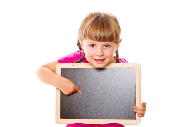 Bambina che tiene bordo nero sulla parete bianca