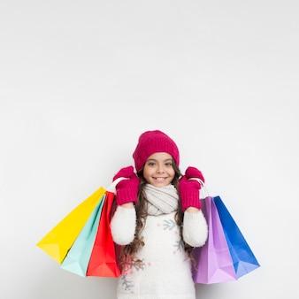Bambina che tiene i sacchetti della spesa stagionali