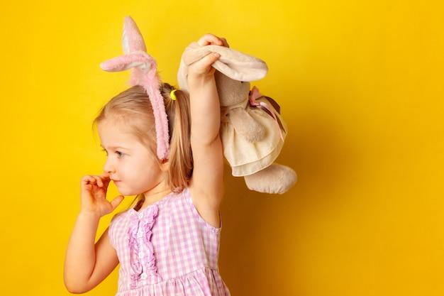 Bambina che tiene il suo giocattolo del coniglietto contro la superficie gialla