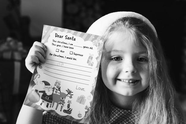 Bambina che tiene la sua lista dei desideri di natale