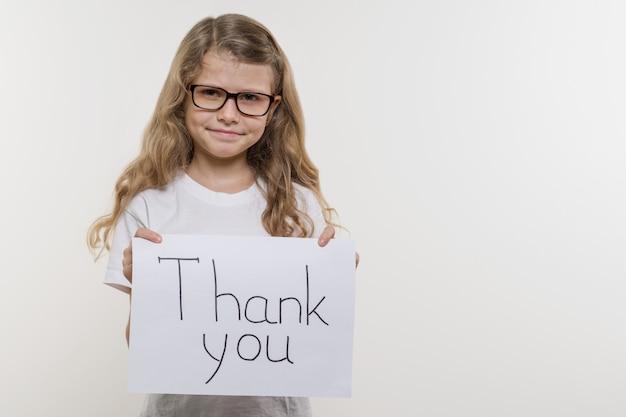 Bambina che tiene pezzo di carta con la parola grazie