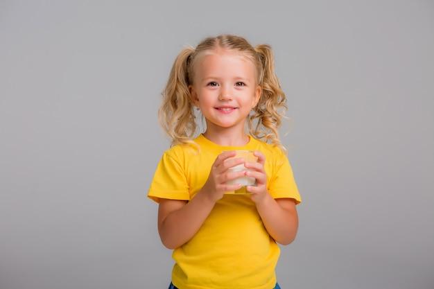 Bambina che tiene un bicchiere di latte su uno sfondo chiaro, spazio per il testo