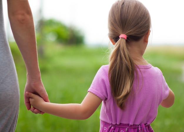 Bambina che tiene una mano di sua madre. concetto di relazioni familiari.