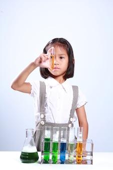 Bambina che tiene una provetta con liquido, chimica di scienziato ed educazione scientifica
