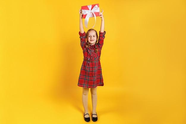 Bambina che tiene una scatola con un regalo sopra la sua testa.