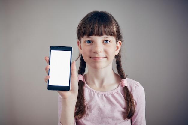 Bambina che tiene uno smartphone con uno schermo bianco