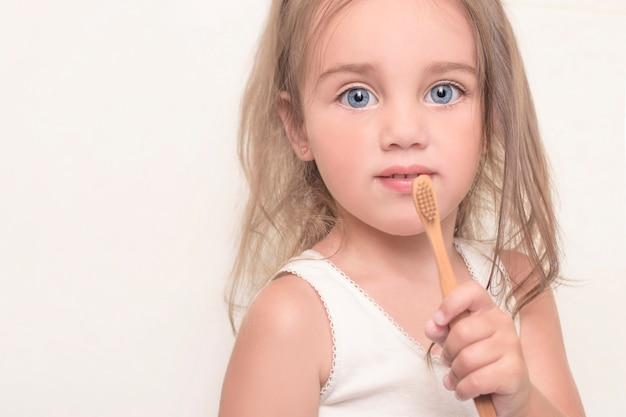 Bambina che tiene uno spazzolino da denti di bambù in sue mani. concetto di salute dentale. copia spazio