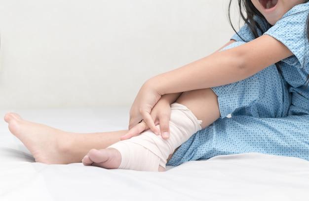 Bambina che tocca la caviglia con bendaggio elastico, gamba rotta, doloroso e concetto di assistenza sanitaria