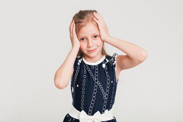 Bambina che tocca la sua testa con entrambe le mani