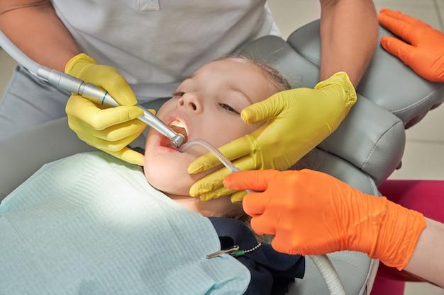 Bambina che tratta i denti nella clinica di odontoiatria.