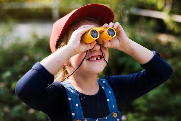 Bambina che usando il binocolo