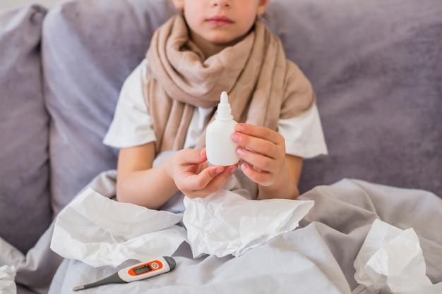 Bambina che usando spray naso