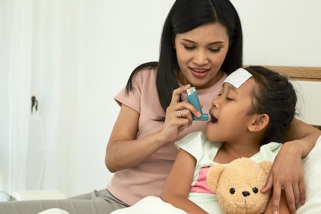 Bambina che utilizza l'inalatore per l'asma