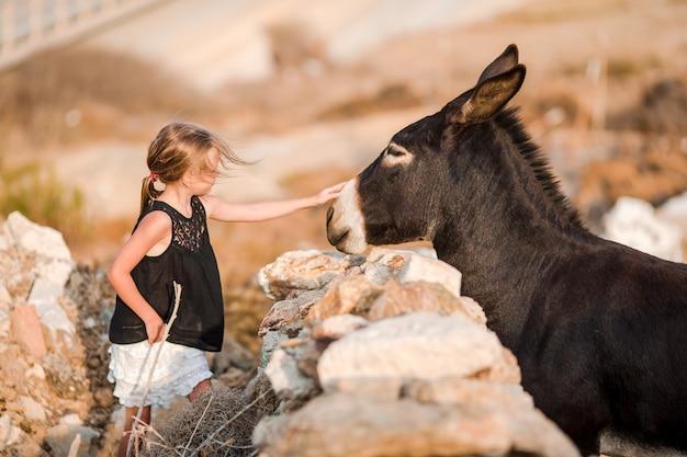 Bambina con asino sull'isola di mykonos