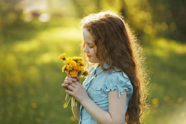 Bambina con bouquet di denti di leone gialli.