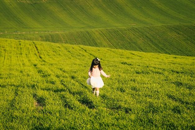 Bambina con camicia rosa e gonna in un prato. faccia disgustata. non le piace il campo