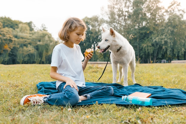 Bambina con cane bianco husky seduto sul prato