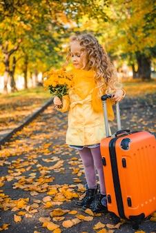 Bambina con capelli biondi in autunno sfondo con fiori e valigia