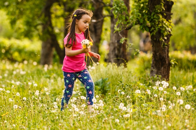 Bambina con capelli biondi lunghi che stanno nel campo con il mazzo dei fiori in sue mani al giorno soleggiato di bella estate