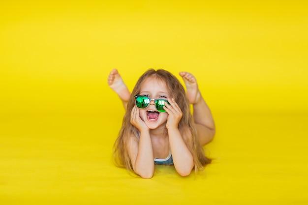 Bambina con capelli marroni in costume da bagno blu che posa sul fondo giallo